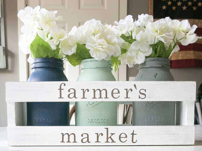 White wooden crate with farmer's market painted on it and three painted mason jars inside with white faux flowers