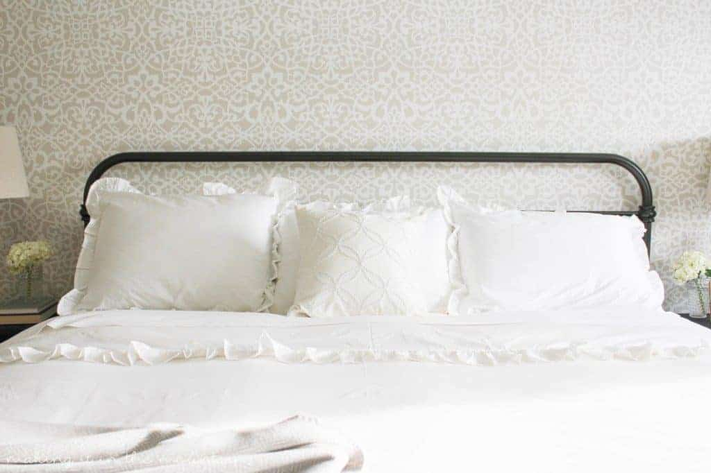 White farmhouse bedding on large iron bed with stenciled wall behind the bed