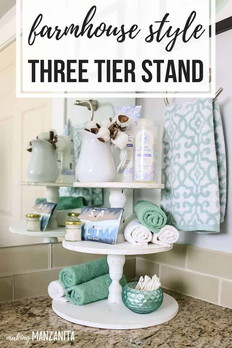 white wood three tier stand with teal and white bathroom accessories  sitting on a bathroom counter with overlay text that says farmhouse style three tier stand