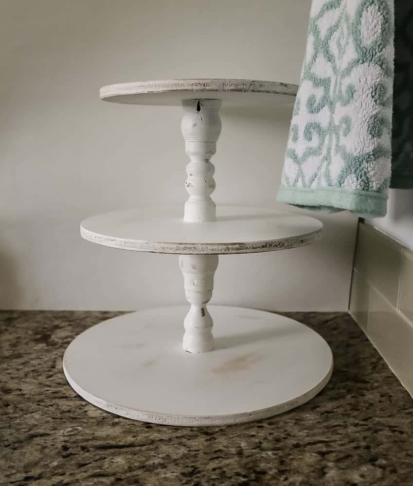 White painted and distressed farmhouse wooden stand with three levels on a bathroom counter