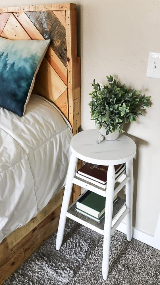 white stool with two shelves under it next to a bed, with a plant on the stool and books on the shelves
