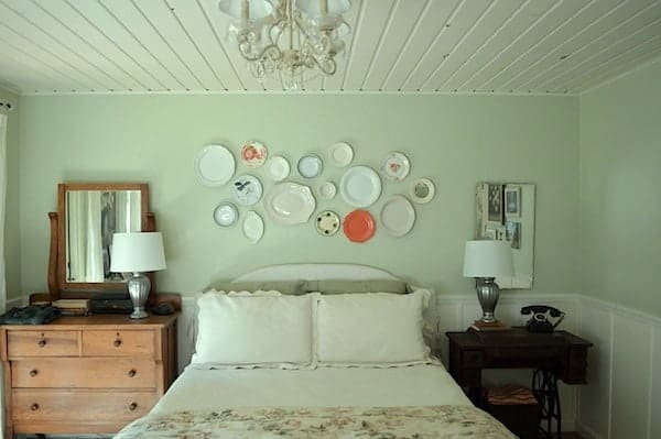 Bedroom showing a white planked ceiling, white chandelier, vintage plate wall hanging as over the bed decor, white wedding, and dresser used as a nightstand
