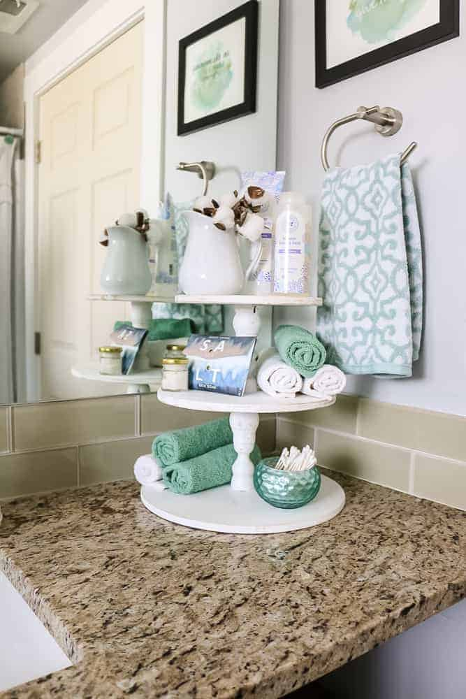 Three tiered farmhouse stand painted white in the corner of the bathroom counter decorated with bathroom accessories like lotion, rolled washcloths, and q-tips