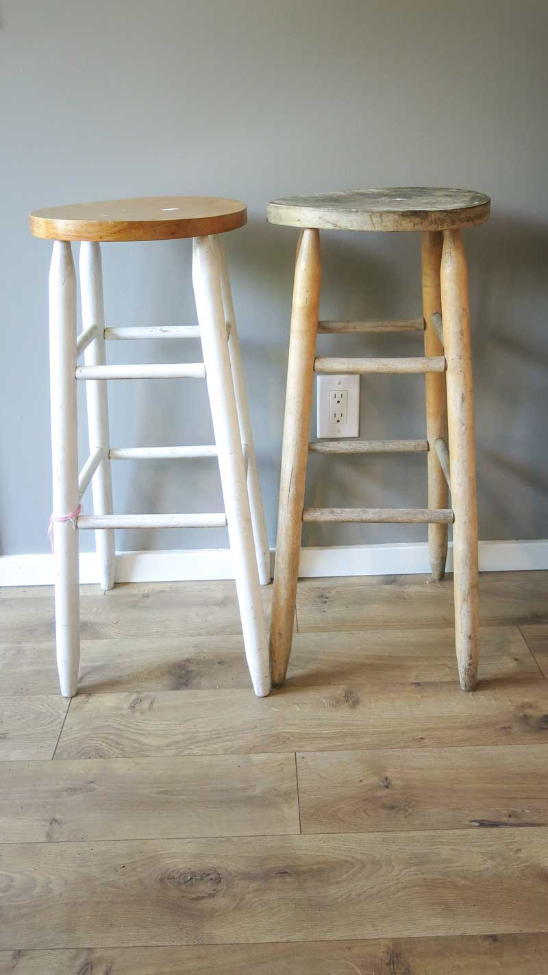 two stools, one with a finished wooden seat and white legs, the other completely unpainted and unfinished