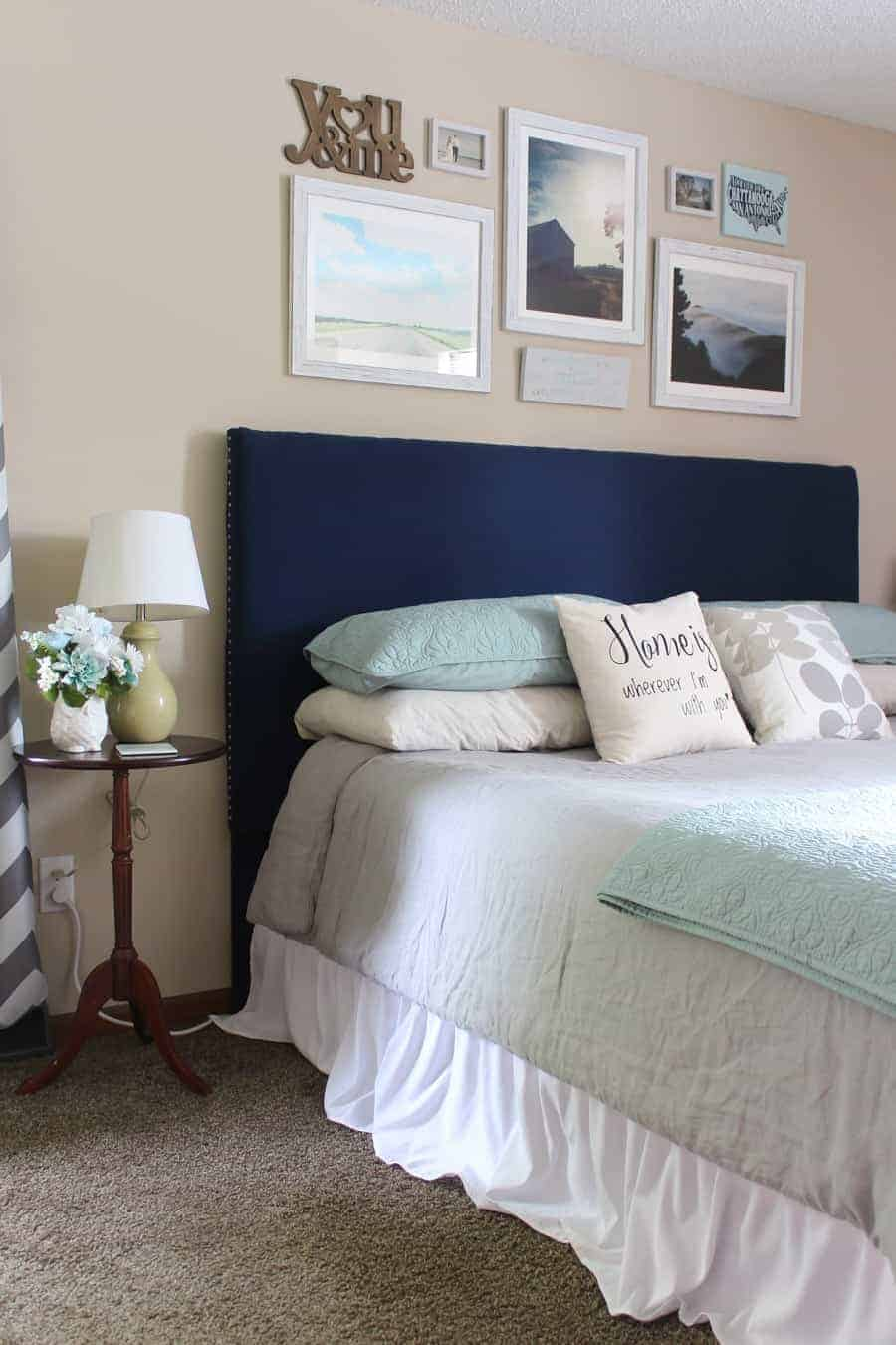 Tan walls in bedroom with navy headboard and gallery wall hanging for over the bed decor