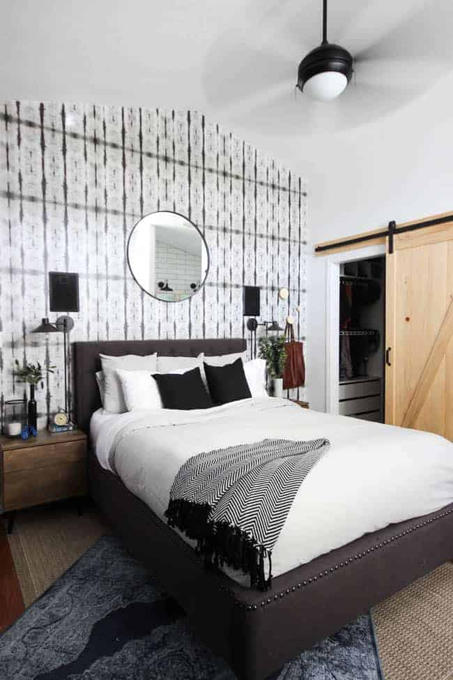 Black and white modern bedroom with patterned wallpaper on the wall behind bed with a large round mirror hanging on it. Room has a light wood barn door, black ceiling fan and white bedding on the dark gray bed