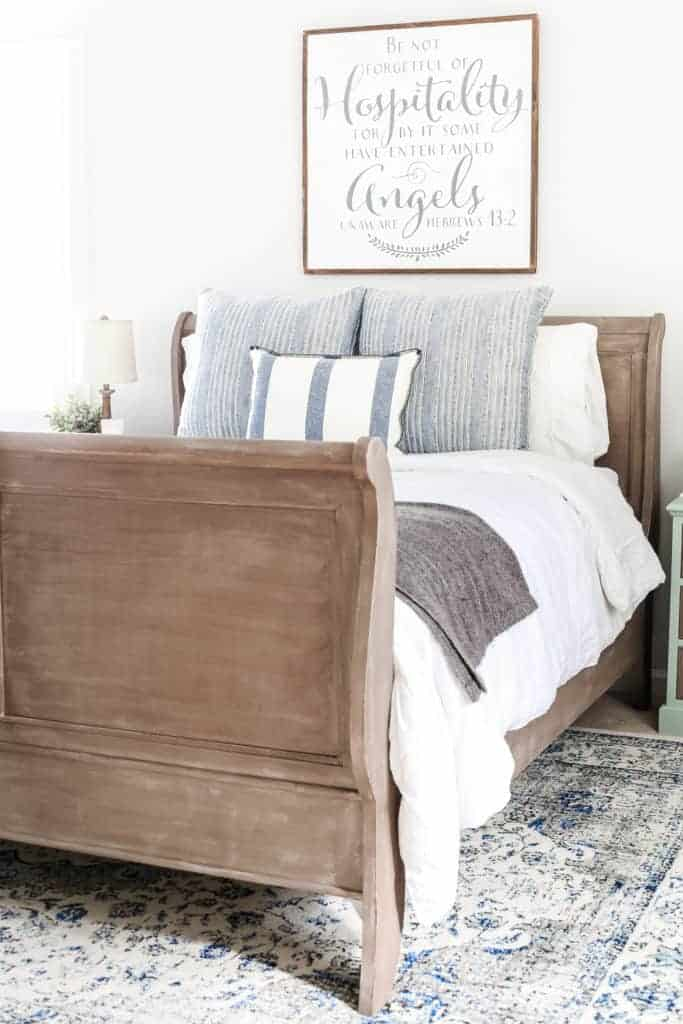 blue cottage style guest bedroom with farmhouse sign above bed