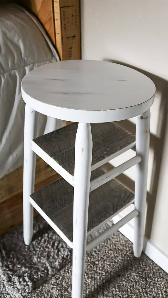 white stool with two shelves next to a bed