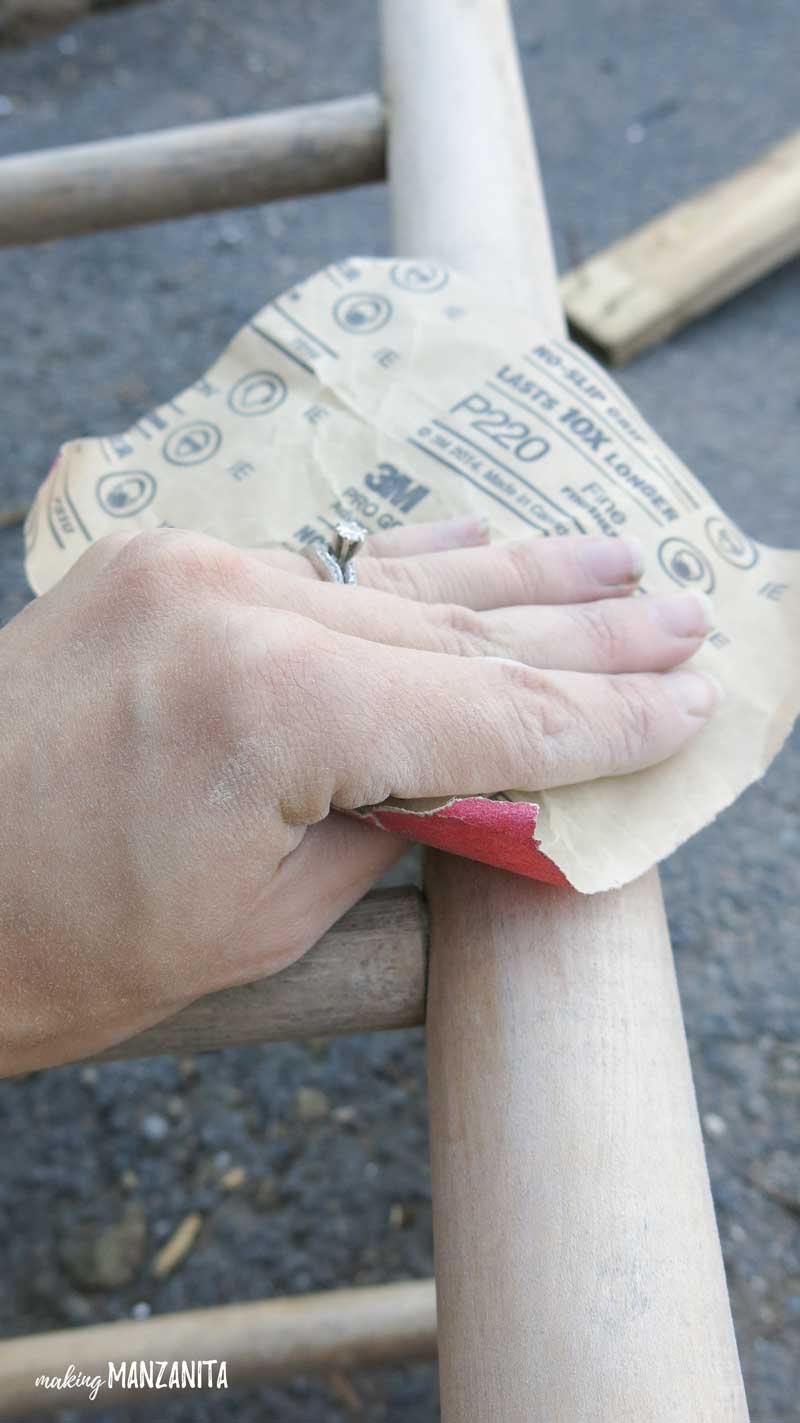 a hand using sandpaper on a wooden stool leg