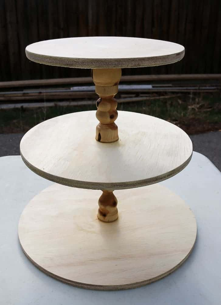shows an unfinished wood three tier stand outside