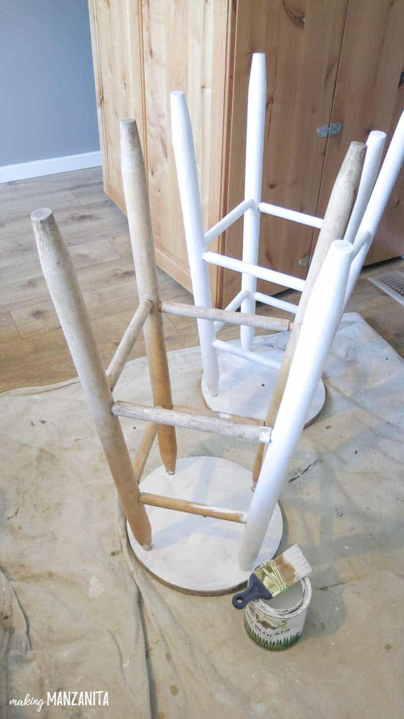 2 bar stools turned upside down with white primer painting in progress