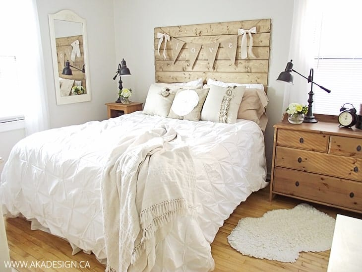 Farmhouse style bedroom with wood plank headbard, white farmhouse bedding, and wood nightstand