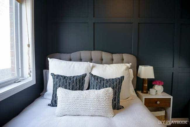 Dark square board and batten accent wall behind bed with gray upholstered bed with white bedding