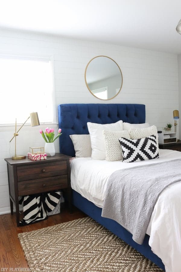 Blue upholstered bed with white bedding, jute rug, wood nightstands, white shiplap wall and gold round mirror hanging as over the bed decor