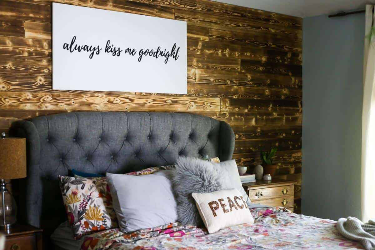 DIY wood planked accent wall in a bedroom behind a gray upholstered bed with floral bedding with a sign on wall that says always kiss me goodnight