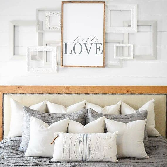 White layered frames and large farmhouse sign that says hello love hanging on a white shiplap wall over a bed with gray and white bedding