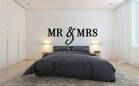 White modern looking bedroom with a gray bed, large white wall behind the bed with wall sign with large letters that says Mr & Mrs