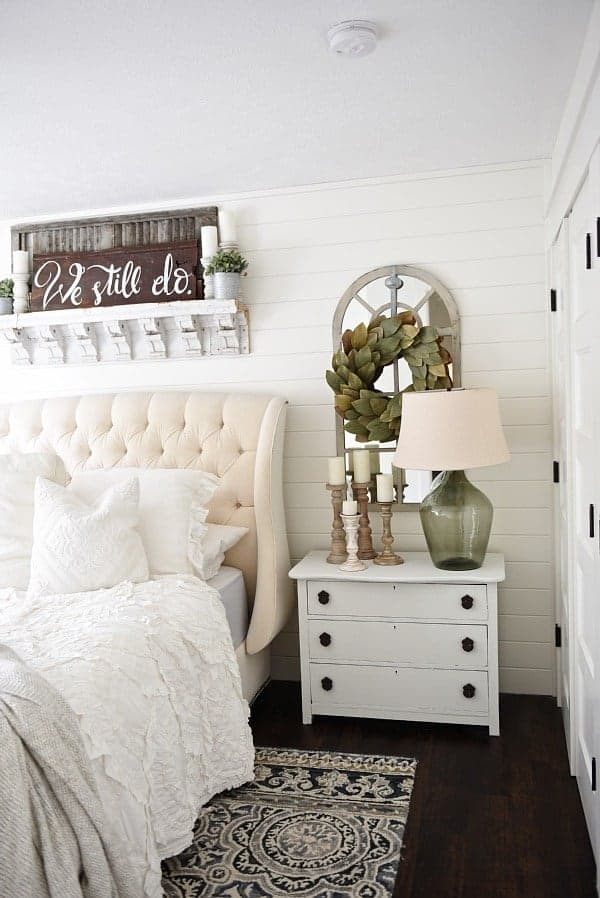 Farmhouse style bedroom with white tufted bed, white bedding, shiplap wall, white painted nightstand, shelf with vintage corbels hanging over bed with a farmhouse sign that says we still do