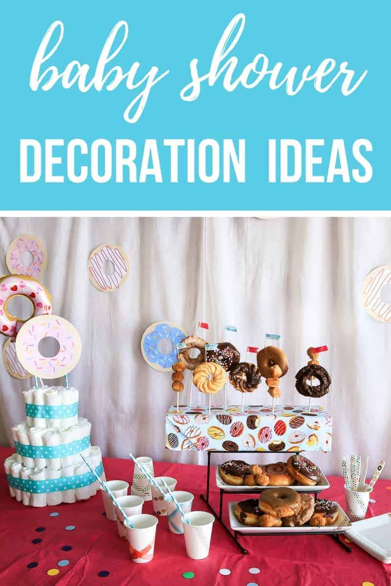 Baby shower food table on bright pink table cloth with diaper cake and donuts with text overlay that says baby shower decoration ideas