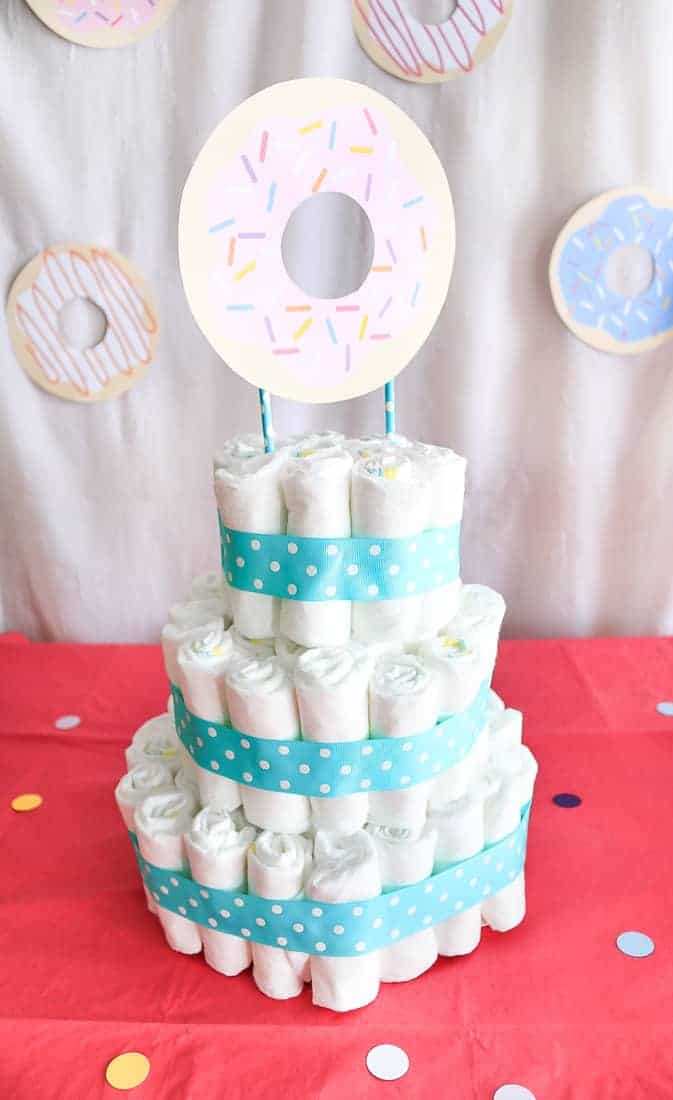 Three tiered diaper cake with blue polka dot ribbon wrapped around it and a paper donut cake topper