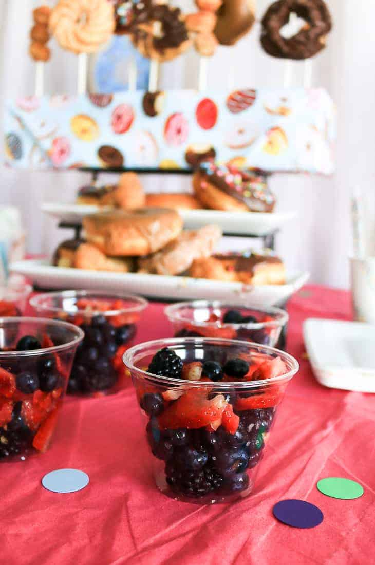 Blueberries, blackberries and strawberry fruit cups in clear plastic cups with donuts in the background