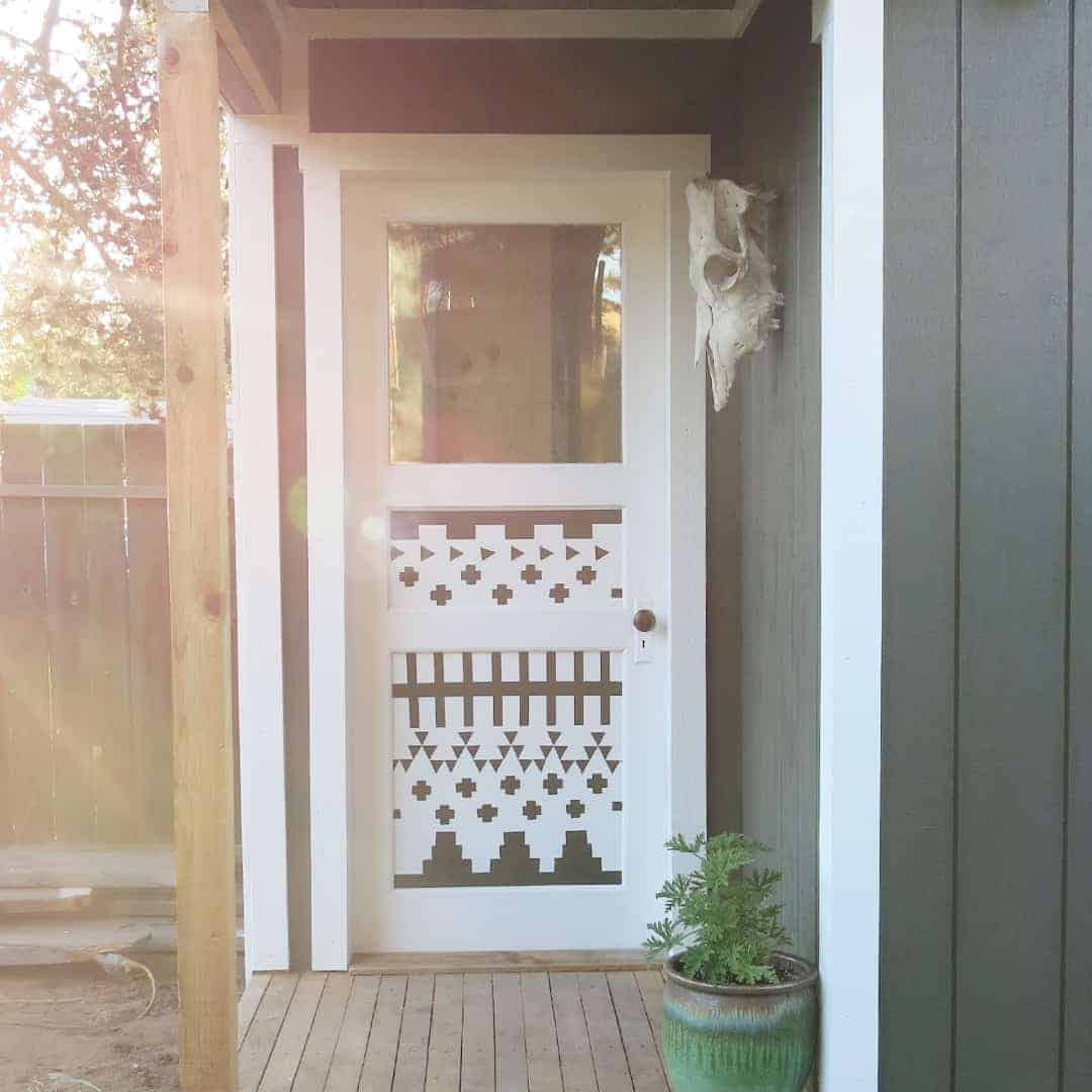 Photo of white door with decorative boho style painted design on a green garden shed.