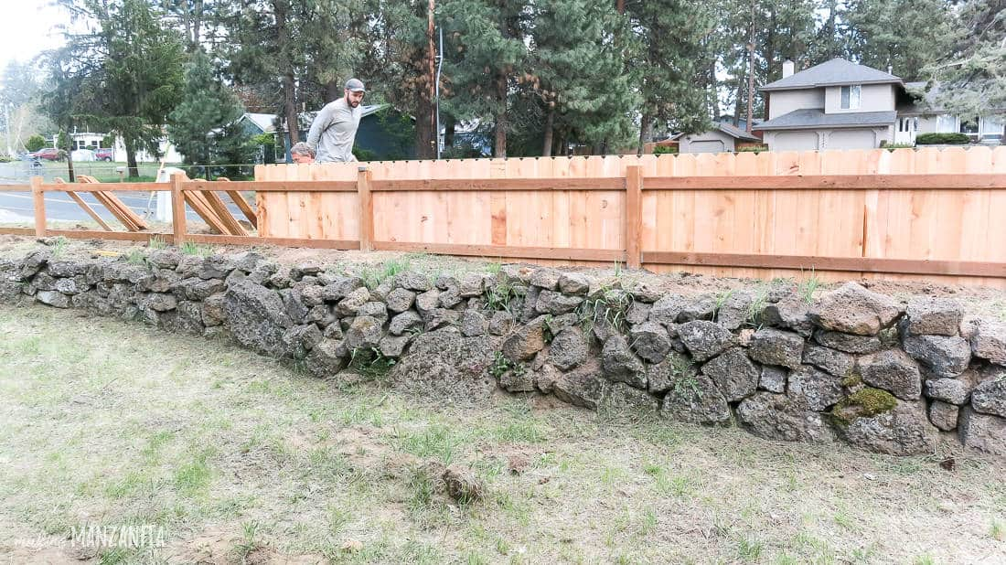 Photo of short cedar fence being built on a ledge