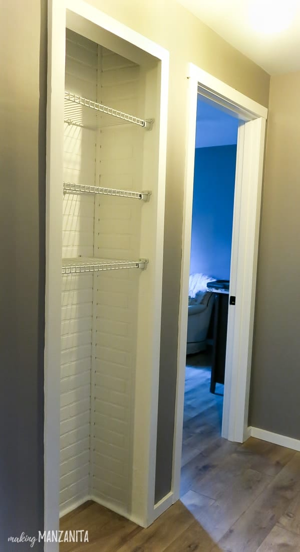 Hallway closet with white faux bricks and white wire shelving