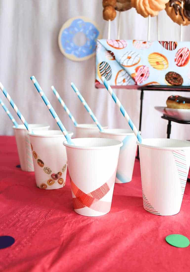 Rows of white paper cups with blue straws on a bright pink table cloth
