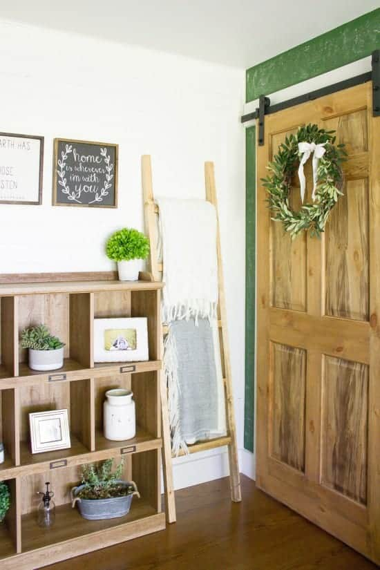 White barn door with wreath and ladder with blankets hanging on rugs and shelves decorated with farmhouse decor