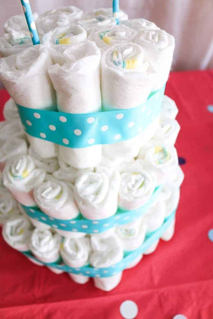 Donuts rolled up and stacked together to form a tiered cake formation for a diaper cake at a baby shower
