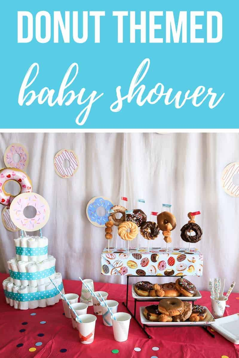 Text overlay on top of photo that says donut themed baby shower. Photo on bottom half shows diaper cake, white paper cups and a tiered stand with donuts on a bright pink table cloth