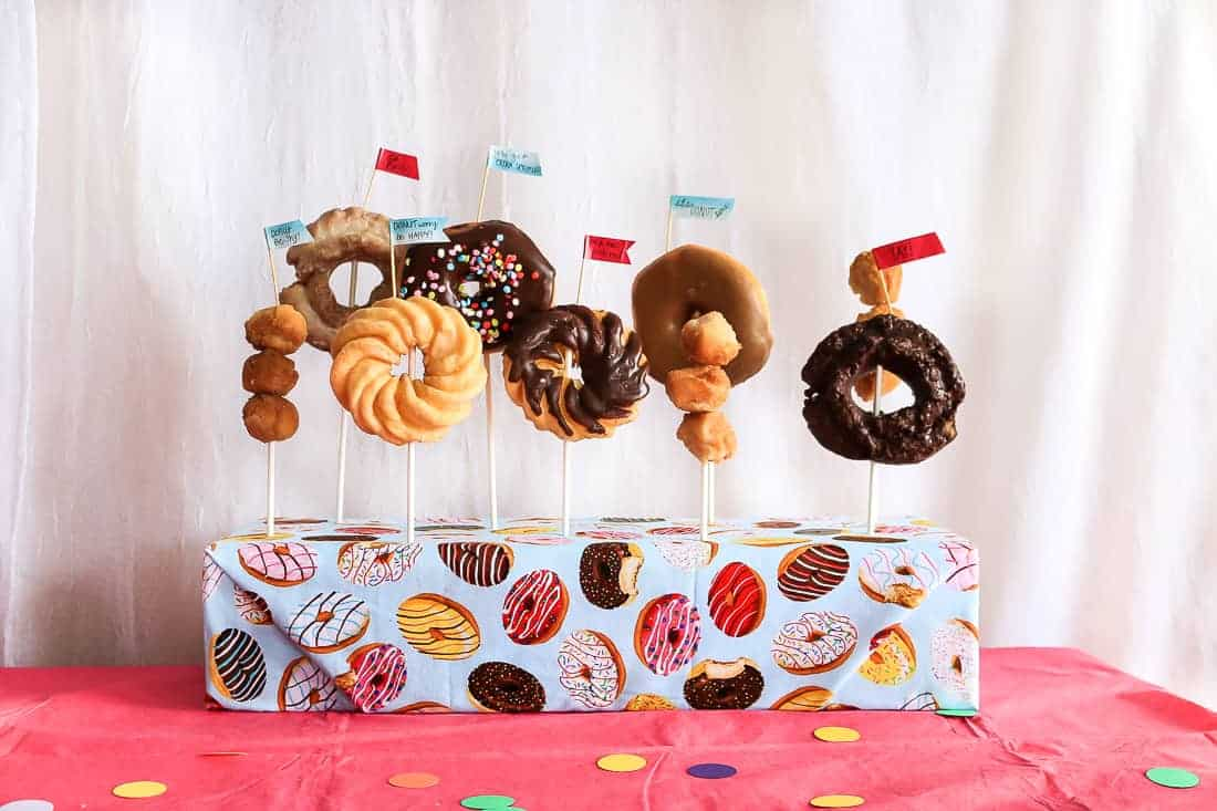 Donut stand on a pink party table with different kinds of donuts.