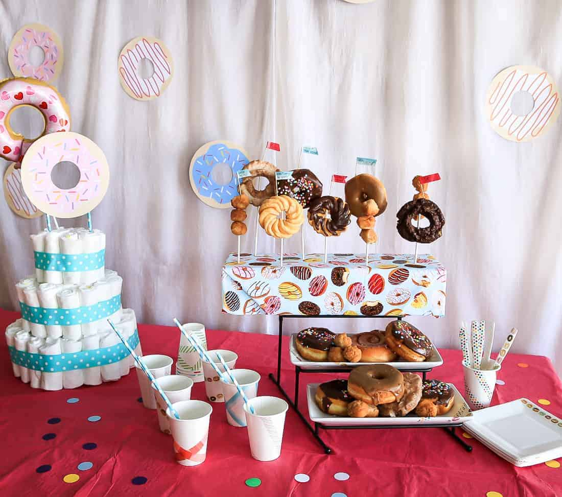 Bright pink tablecloth on table displaying donuts on a tiered stand along with a cake made out of diapers and paper cups with straws
