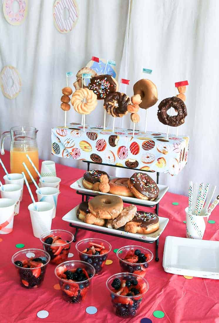 Donut stand in the center of the table along with other party foods like orange juice, mixed berries, cups and stirrers and spoons.