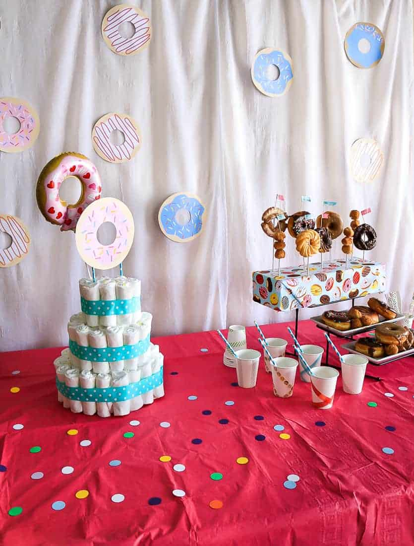 White background with paper donuts behind a bright pink table with food displayed for a baby shower
