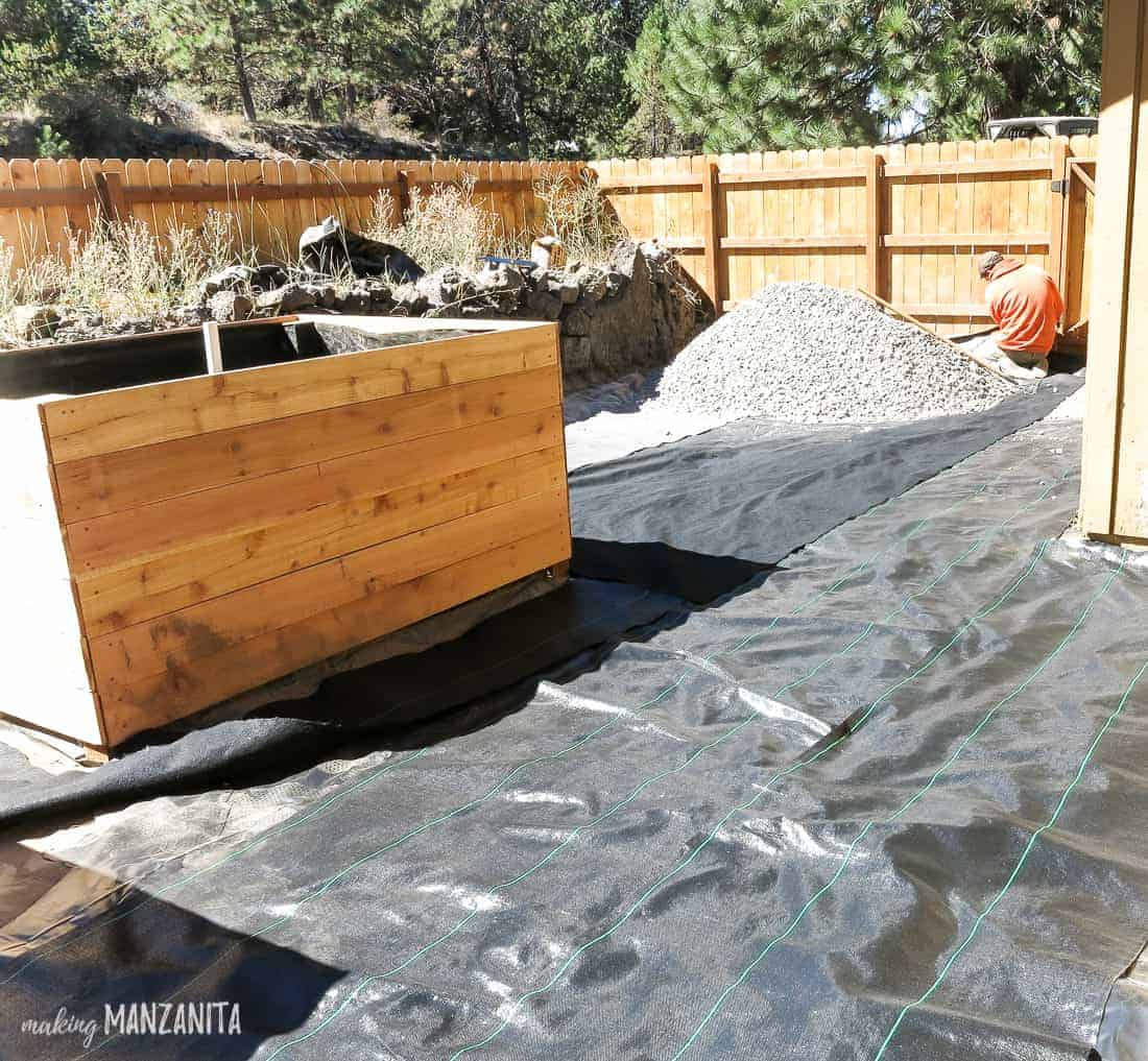Black landscape fabric laid out on ground around garden beds and large pile of gravel, which will be spread over fabric.