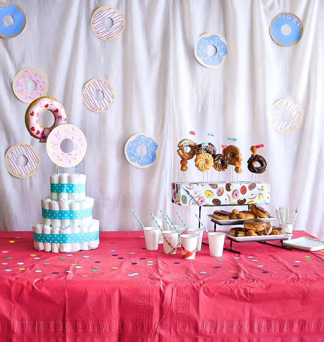 Food display at a baby shower showing a diaper cake and donuts with a white background and paper donuts