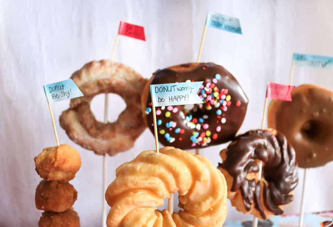 Toothpick flags made with washi tape sticking out of donuts