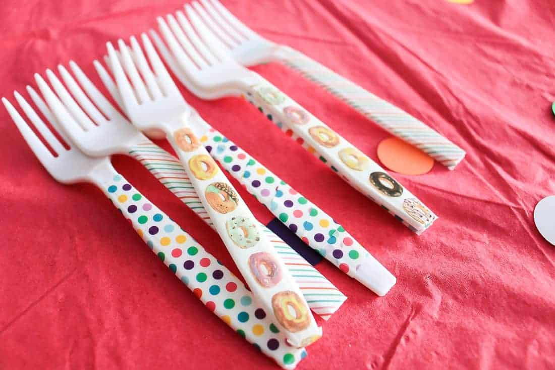 Plastic forks laying on a pink tablecloth with colorful washi tape wrapped around the handle of the forks.