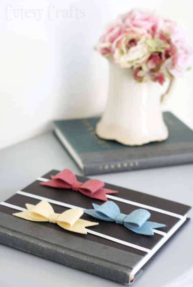 Flowers in vase show in background and book with 3 elastic bookmarks on the cover that feature felt bows