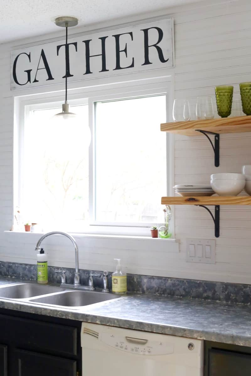 Kitchen with open shelving and window above sink with farmhouse sign above window that says gather