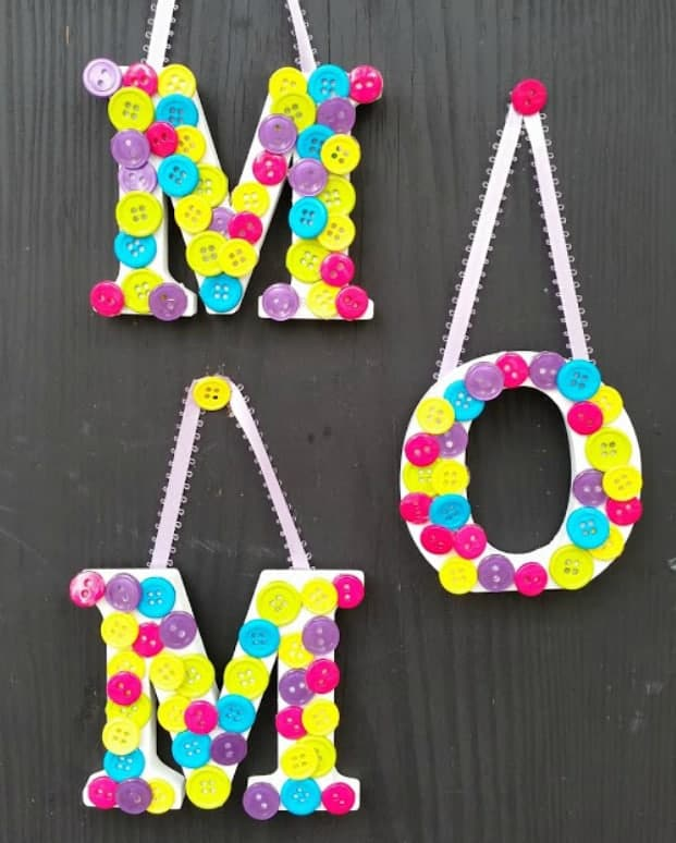 Three letters spelling M-O-M covered in yellow, purple, pink and blue buttons hung on wall