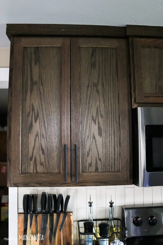 Dark wood upper kitchen cabinet that goes all the way to the ceiling with sleek and modern black cabinet handles