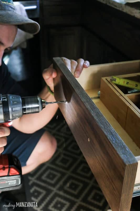 Man shown drilling holes in front of kitchen cabinet drawer to install drawer pull