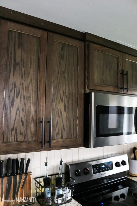 Upper kitchen cabinets with dark wood and modern farmhouse cabinet hardware