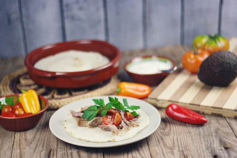 Taco meal shown on colorful plates with peppers, tortillas and avocados in the background. The plates are on top of a pallet wood backdrop perfect for food photography