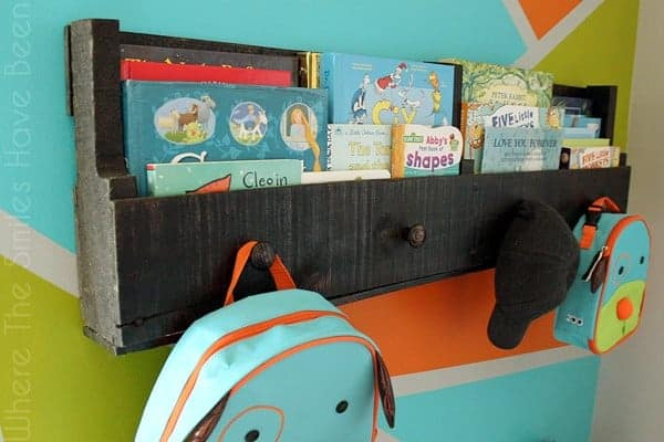 Pallet wood bookshelf hanging on wall with books and backpacks
