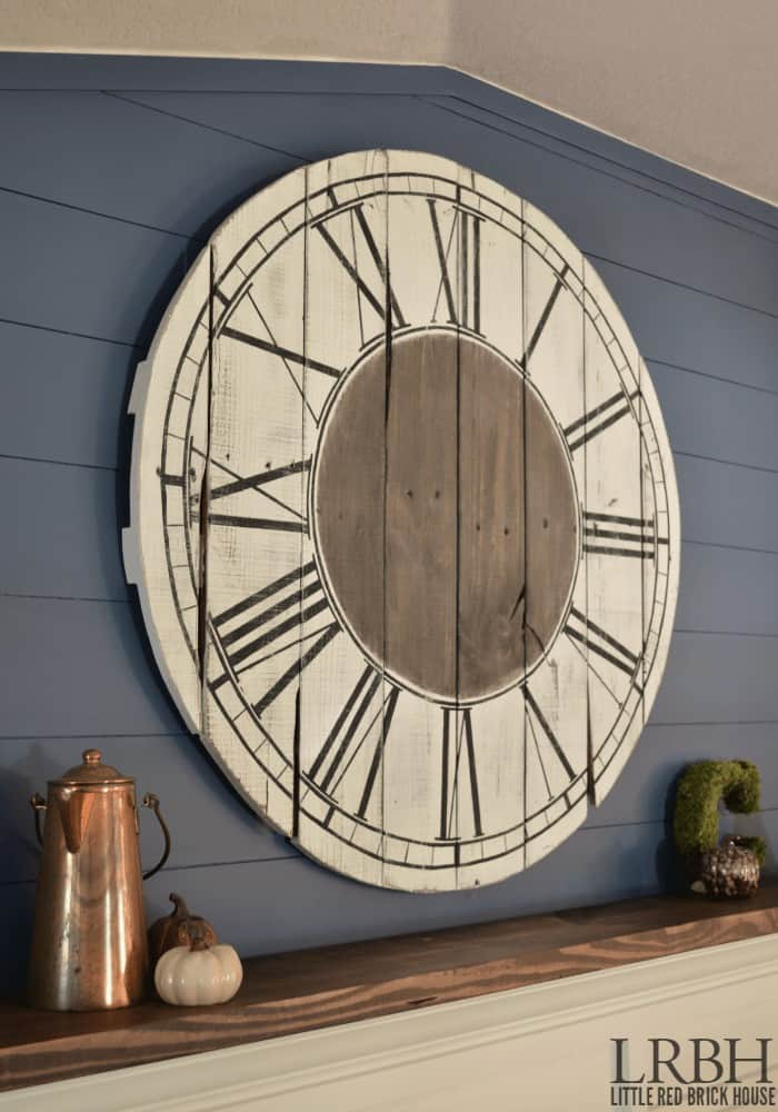 Round clock with roman numerals painted on it hanging on wall
