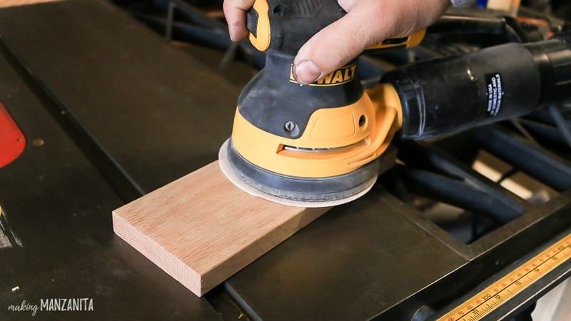 Man holding sander on trim piece